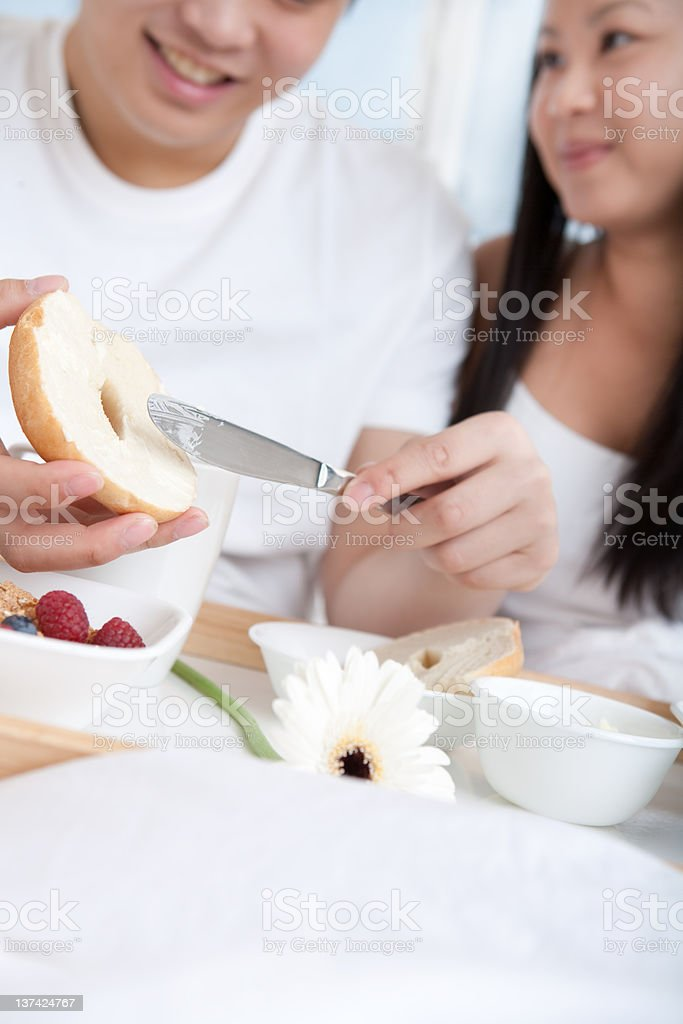 Asian young couple eating breakfast in bed royalty-free stock photo