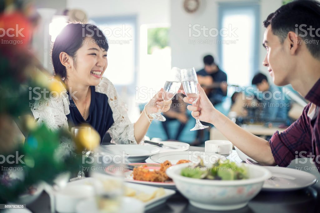 Asian young couple enjoying a romantic dinner  evening drinks while sitting at the dinning table on the kitchen together stock photo