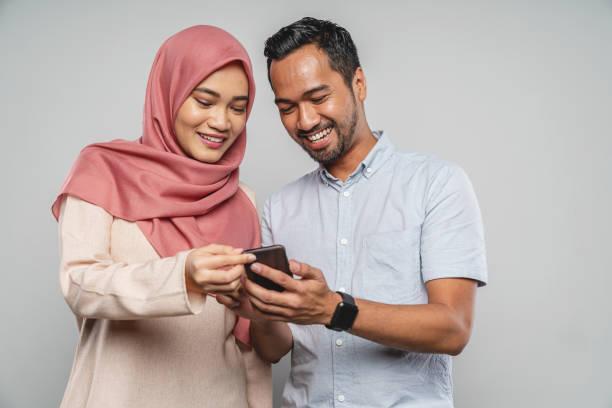 asiatique jeune couple avec téléphone intelligent - business malaysia photos et images de collection