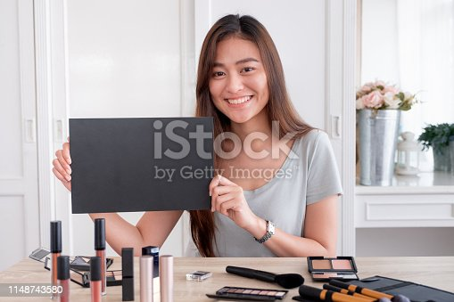 1125605742istockphoto Asian young female blogger giveaway gift fan following channel while recording vlog video with makeup cosmetic at home online influencer concept.live streaming viral.mock up blackboard for your design 1148743580