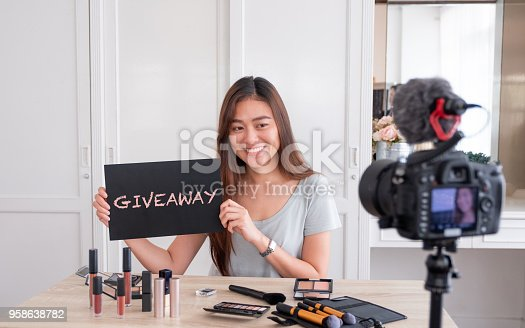 istock Asian young female blogger giveaway gift to fan following channel while recording vlog video with makeup cosmetic at home online influencer on social media concept.live streaming viral. 958638782
