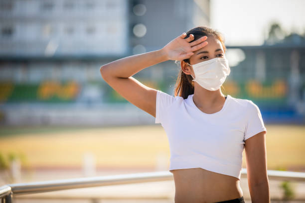 Asian Young fitness sport woman is resting tired and she wears a mask for protective Dust and pollution on city Asian Young fitness sport woman is resting tired and she wears a mask for protective Dust and pollution on city race distance stock pictures, royalty-free photos & images
