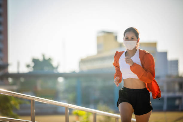 Asian Young fitness sport woman running  and she wears a mask for protective Dust and pollution and protection flu virus, influenza, coronavirus on city Asian Young fitness sport woman running  and she wears a mask for protective Dust and pollution and protection flu virus, influenza, coronavirus on city race distance stock pictures, royalty-free photos & images