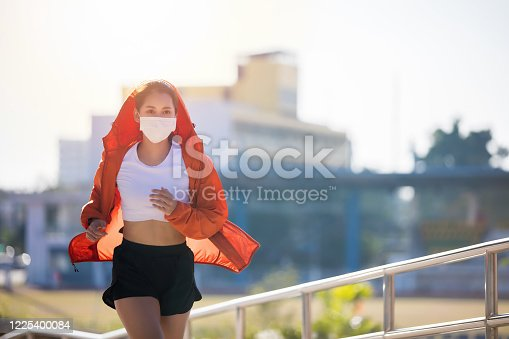 Asian Young fitness sport woman running  and she wears a mask for protective Dust and pollution and protection flu virus, influenza, coronavirus on city