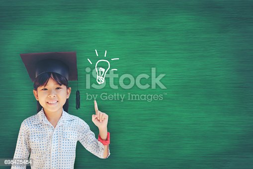 istock Asian Young girl has a bright idea as she stands against the blackboard at school 698425484