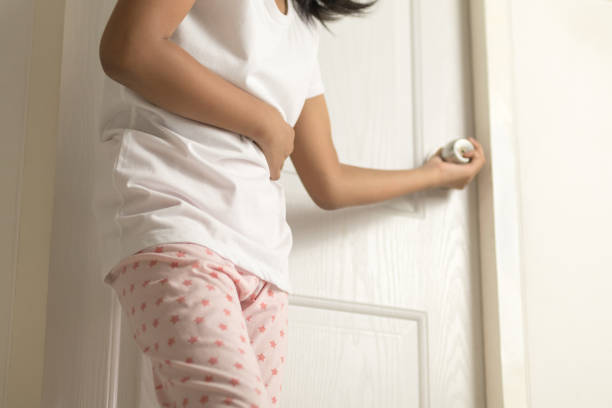 asian young girl has stomach pain and standing in front of the toilet at home - diarrhea stock pictures, royalty-free photos & images
