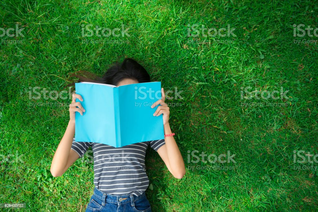 Asian young girl reading book on park top view foto stock royalty-free