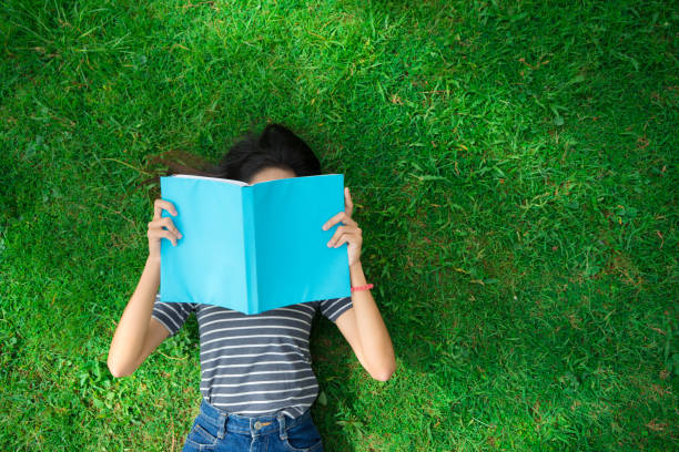 Asian young girl reading book on park top view stock photo