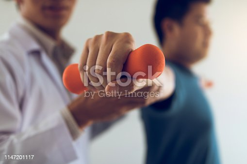 950649706istockphoto Asian young male physiotherapist helping patient with lifting dumbbells exercises in office. 1147201117