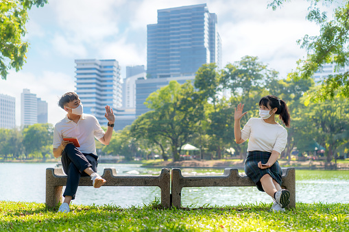 Asian Young Man And Woman Greet And Say Hello With They Friend And Wearing Mask Sitting Distance Of 6 Feet Distance Protect From Covid19 Viruses For Social Distancing For Infection Risk In Park Stock Photo - Download Image Now