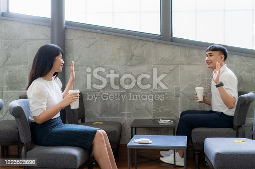 Asian young man and woman sitting one person per one table and greet and say hello for distance of 6 feet distance protect from COVID-19 viruses for social distancing for infection risk at coffee cafe.