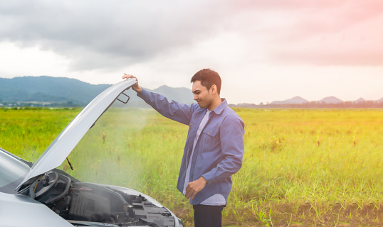 Asian young man having trouble car engine overheating and have smoke. Automotive motor problem concept.