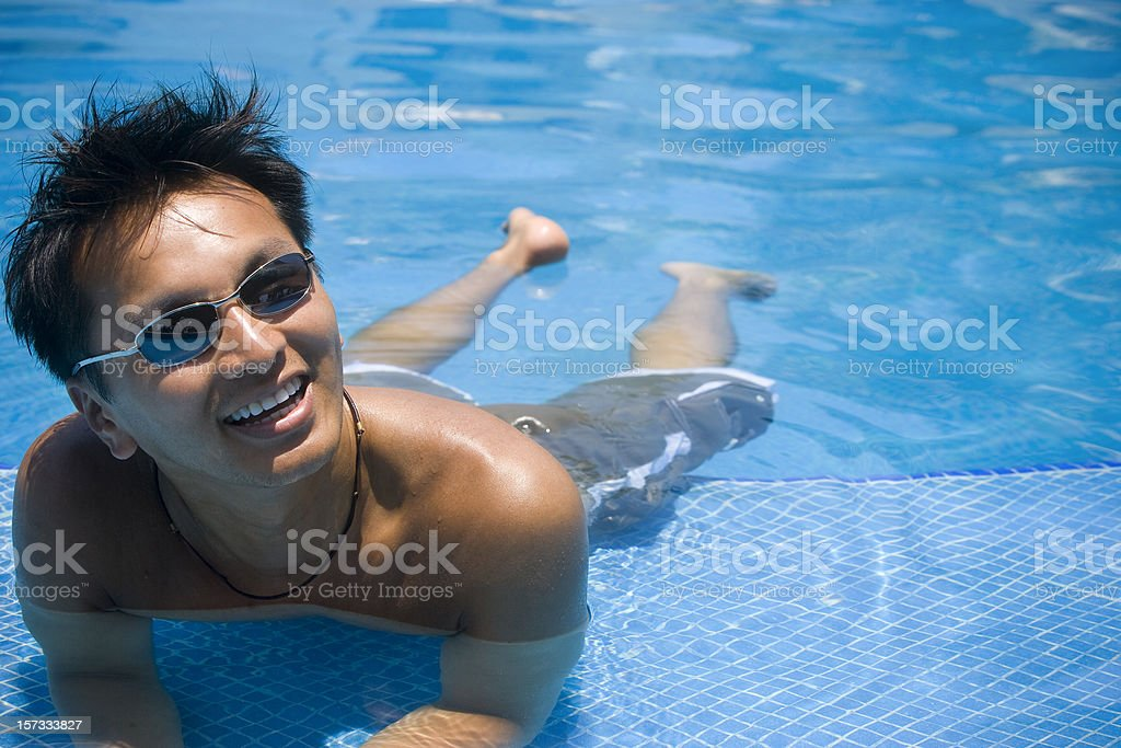 Asian Young Man Portrait in Sunny Swimming Pool, Copy Space royalty-free stock photo