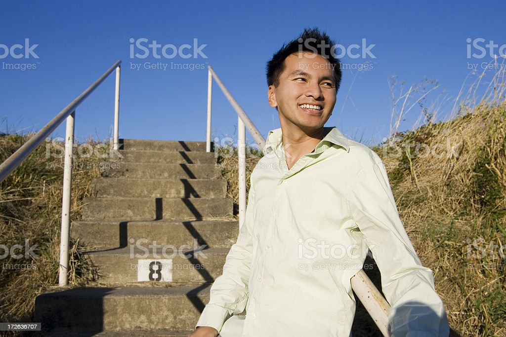 Asian Young Man Portrait Outdoors on Stairs, Clear Sky, Copyspace stock photo