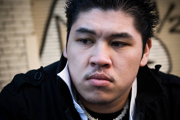 Asian Young Man Portrait Outside, Graffiti Wall in Background stock photo