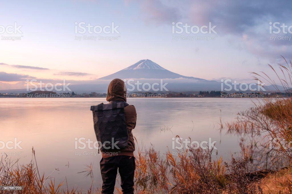 Asian young man stand looking Mount Fuji on Kawaguchiko Lake at dawn stock photo