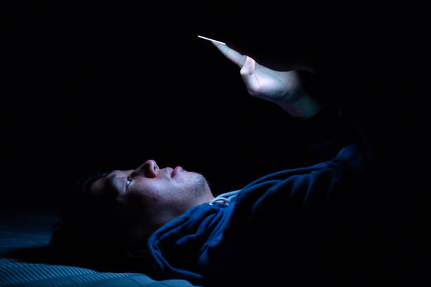 Asiatischer junger Mann mit Handy im dunklen Schlafzimmer mit blauen Licht Handy-Bildschirm - ungesunde Augen Stamm Konzept. – Foto