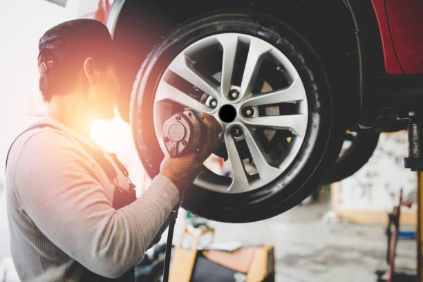 aziatische jonge monteur werkt het apparaat veranderen van banden van auto te houden. reparatieservice. - tyre stockfoto's en -beelden