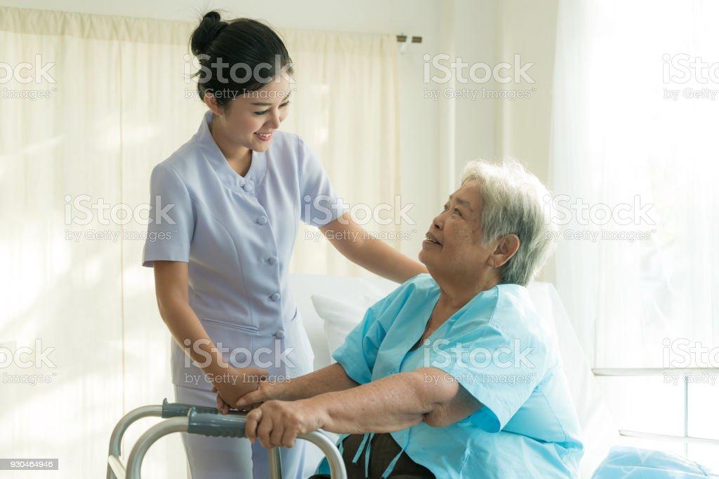 亞洲年輕護士支援老年病人殘疾婦女使用沃克在醫院。老年患者護理理念。圖像檔