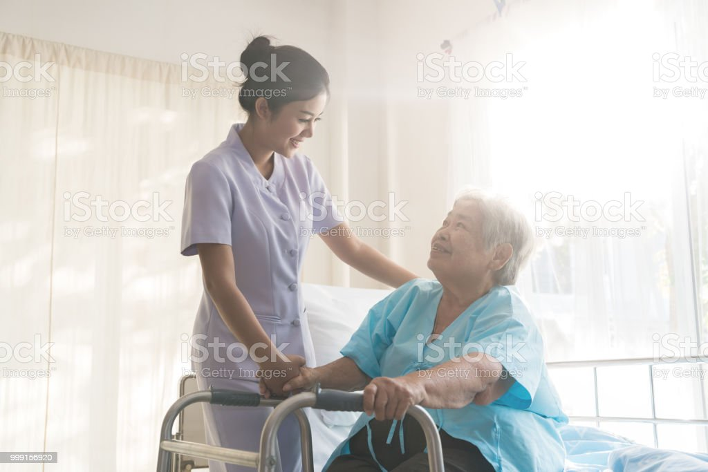 Asian young nurse supporting elderly patient disabled woman in using walker in hospital. Elderly patient care concept. stock photo