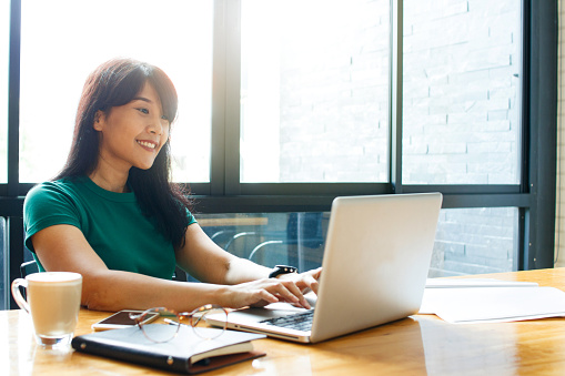 istock Asian young owner business woman working online, checking mail on laptop organizing working process in office. Copy space. 1044799934