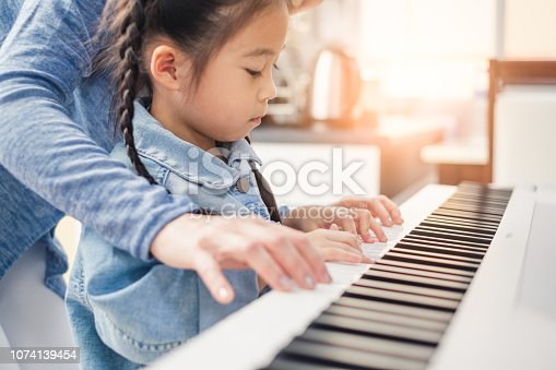 istock Asian young pianist teacher teaching girl kid student to play piano, music education concept 1074139454