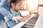 Asian young pianist teacher teaching girl kid student to play piano, music education concept