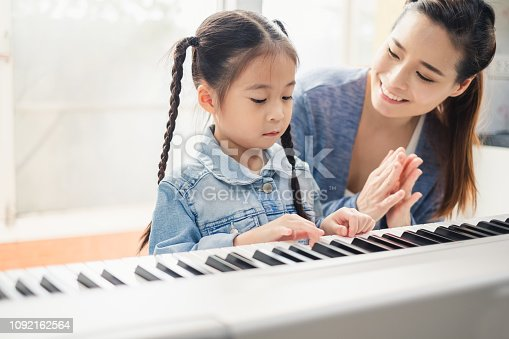 istock Asian young pianist teacher teaching girl kid student to play piano, music education concept 1092162564