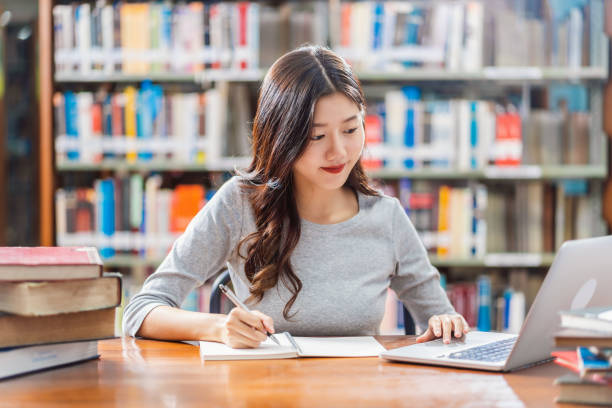 Asian young Student doing homework in library of university