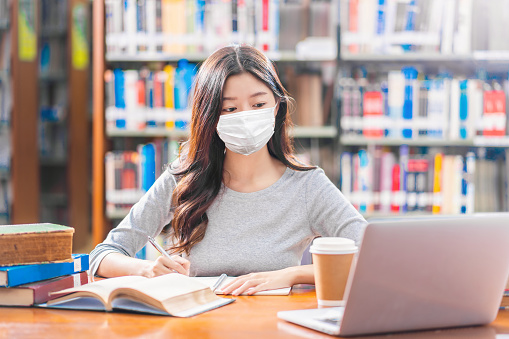 Asian young Student in casual suit wearing surgical mask and doing homework and using technology laptop in library of university or colleage with various book and stationary over book shelf background