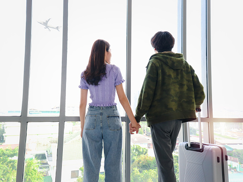 Asian young tourist lover couple hold each other hand, looking through window, standing with luggage suitcase from behind, waiting airline flight at airport terminal, romantic trip on vacation.