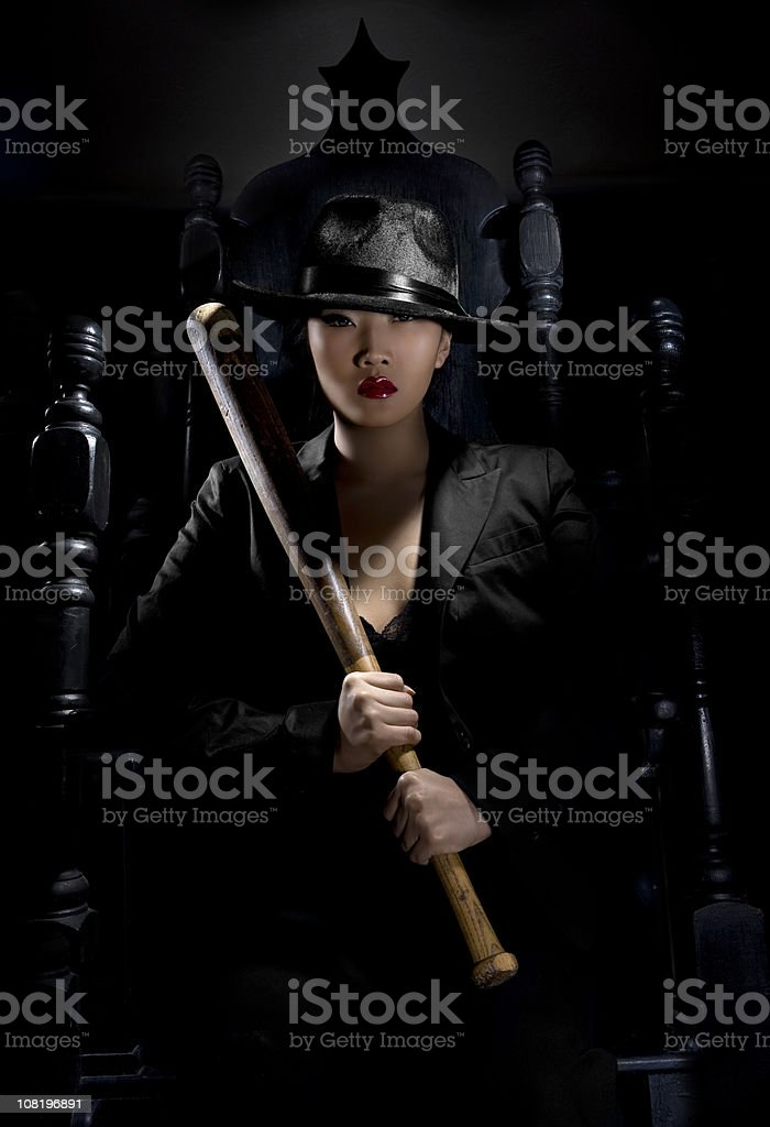 Asian Young Woman as Sexy Gangster Holding Bat on Throne stock photo