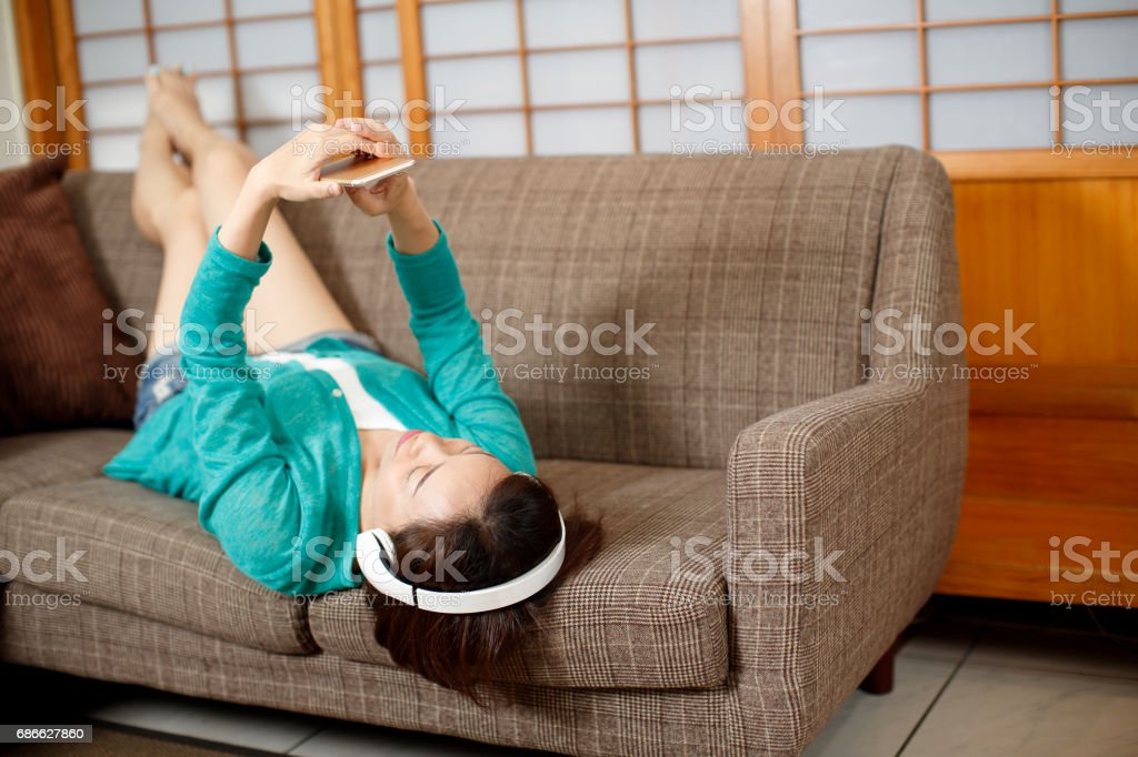 Asian Young woman enjoying listening to music royalty-free stock photo