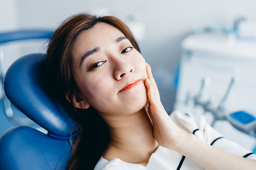 Asian young woman feeling pain, holding her cheek with hand at dentist's office.Toothache concept.
