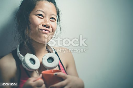 Indoor image of Asian happy young woman holding a cup of coffee, looking at something and making face. She is in bra and hanging headphone on her neck. One person, waist up and selective focus with copy space.