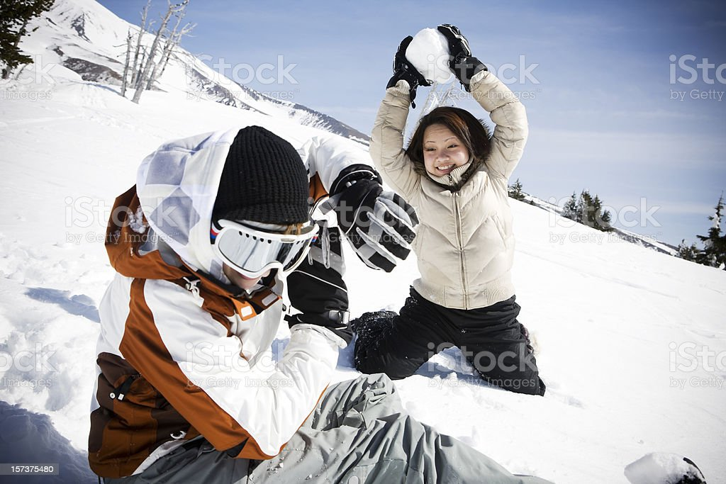 Asian Young Woman in Snowball Fight with Friend on Mountain royalty-free stock photo