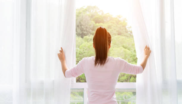 asian young woman opening the curtains and looking out of window - open window imagens e fotografias de stock
