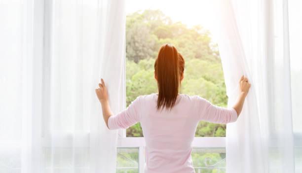 Asiatische junge Frau öffnet die Vorhänge und schaut aus dem Fenster – Foto