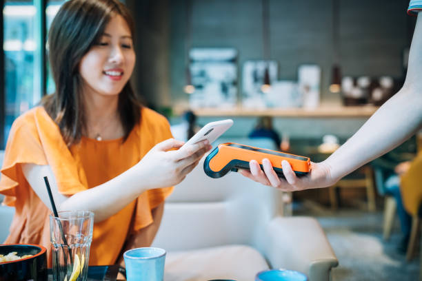 Asian young woman paying with smartphone in a cafe. stock photo