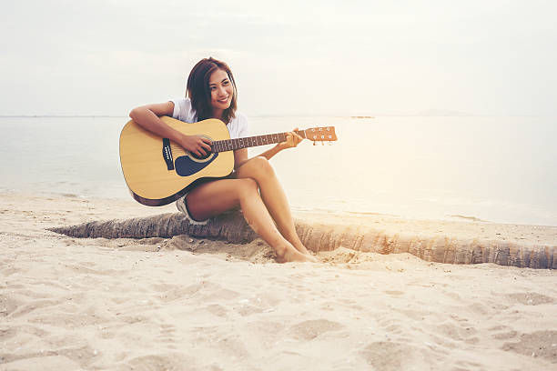 asian young woman playing guitar on the beach - abgeschnittenes t shirt stock-fotos und bilder