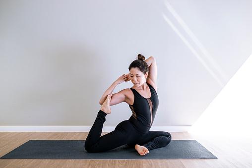 Asian young woman practicing yoga at home - Wellness concept. Eka Pada Rajakapotasana pose.