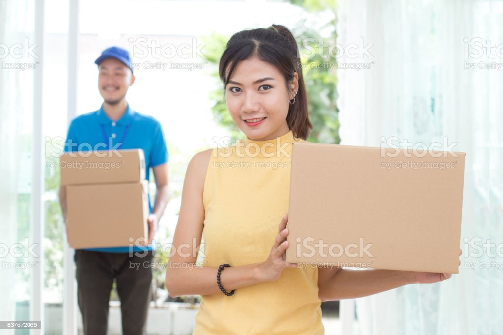 Asian Young Woman receive a Cardboard Box form Man at home, Woman in the foreground is Holding  a Cardboard Box. Delivery Concept. stock photo