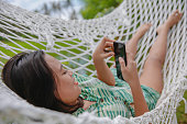 istock Asian Young Woman Relaxing on a Hammock. 1300752861