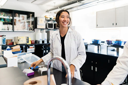 istock Asian young woman student in college science laboratory. 1068513226