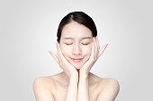 リラックスした表情で顔を触れるアジアの若い女性