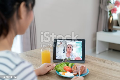 istock Asian young woman virtual happy hour meeting and eating food online together with her mother in video conference with digital tablet for a online meeting in video call for social distancing. 1219748142