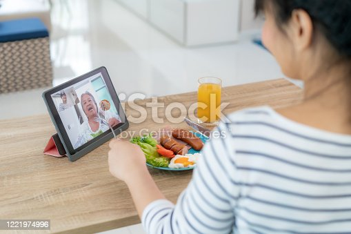 istock Asian young woman virtual happy hour meeting and eating food online together with her mother in video conference with digital tablet for a online meeting in video call for social distancing. 1221974996