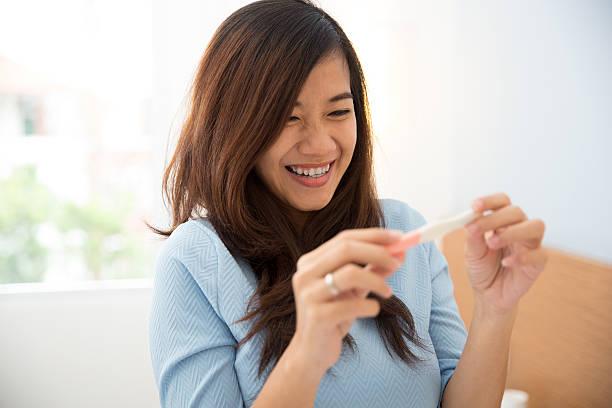 asiatische junge frau mit testpack in der hand - versuche nicht zu lachen stock-fotos und bilder