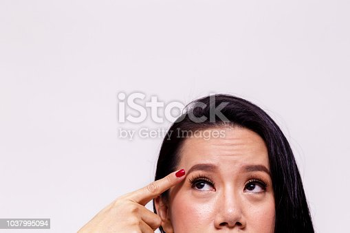 Asian young woman worried and pointing finger towards her aging and old forehead - with copy space - treatment skin care concept