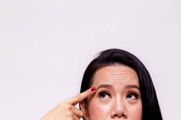 Asiatische junge Frau besorgt und Fingerzeig in Richtung Stirn Altern und alt - mit textfreiraum - Haut Pflege Behandlungskonzept. – Foto